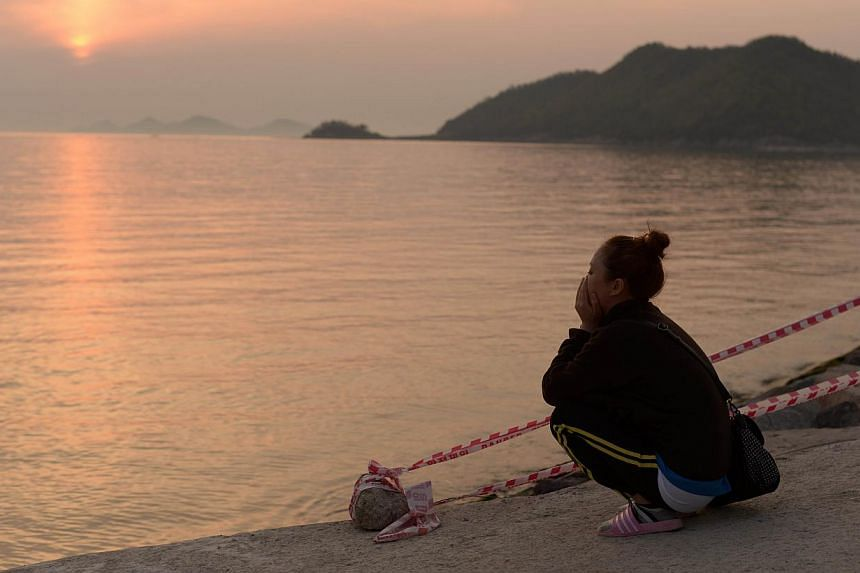A relative of a missing passenger of the Sewol ferry sits next to the sea at Jindo harbour, on April 23, 2014. More than a week after a South Korean ferry carrying 476 people capsized and sank, North Korea finally voiced its condolences Wednesday for