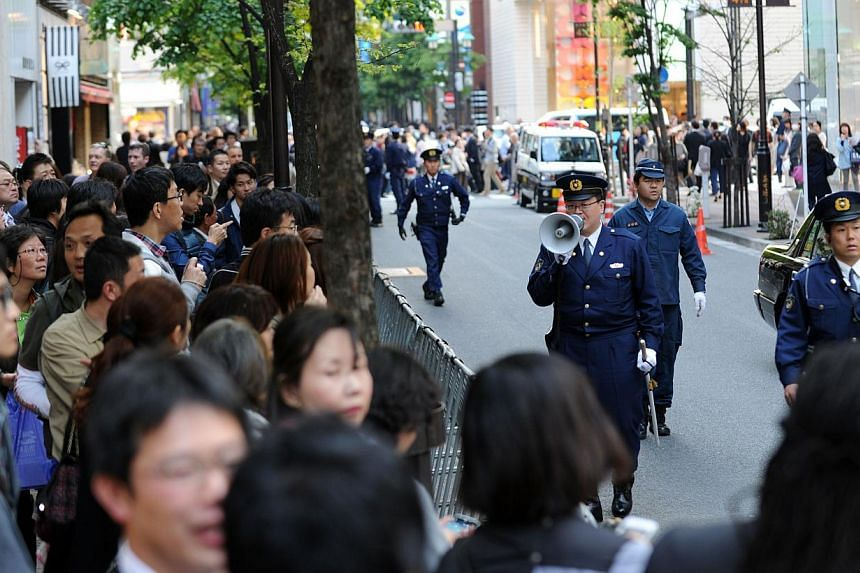 Police officers control the traffic in front of the Sukiyabashi Jiro sushi restaurant at Ginza shopping district in Tokyo, on April 23, 2014, hours before US President Barack Obama's visit. -- PHOTO: AFP
