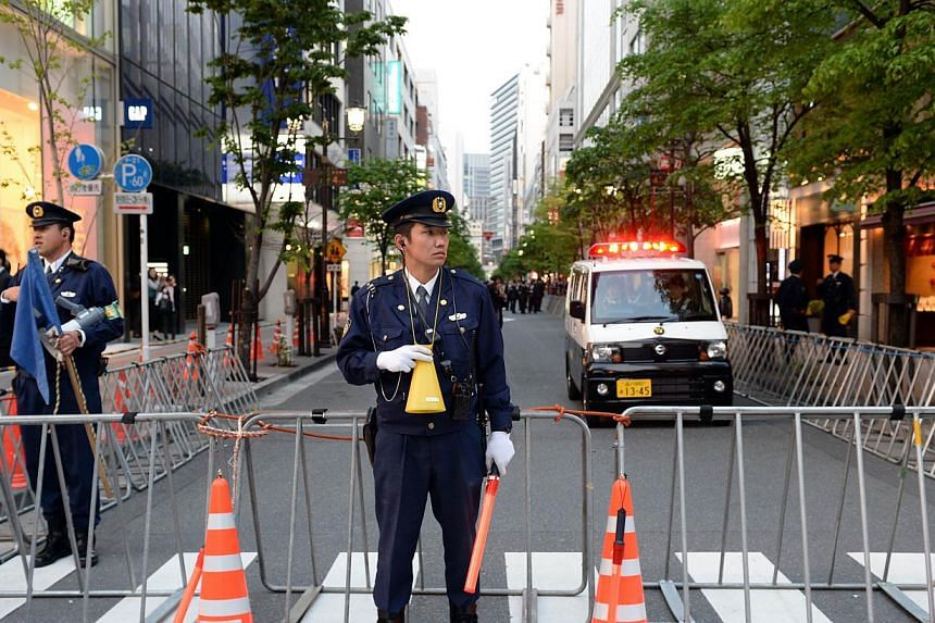 Police officers close the road connecting tothe Sukiyabashi Jiro sushi restaurant at Ginza shopping district in Tokyo, on April 23, 2014, hours before US President Barack Obama's visit. -- PHOTO: AFP