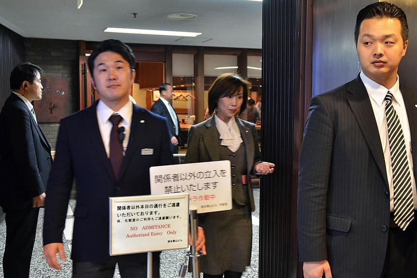 Plainclothes policemen stand guards at the entrance of sushi restaurant Sukiyabashi Jiro in Tokyo, on April 23, 2014. US President Barack Obama will reportedly dine at a tiny Tokyo sushi restaurant on Wednesday, April 23, 2014, - a place with three c
