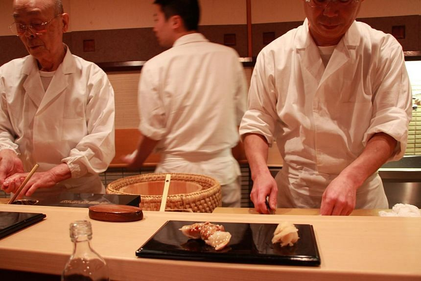 Michelin-starred sushi master Jiro (left) and his elder son, Yoshikazu (right), preparing sushi in Sukiyabashi Jiro restaurant which is located in the basement of an office building in Tokyo's Ginza district. -- ASIAONE FILE PHOTO: SATOKO NISHIMURA