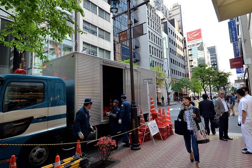 Police officers unload traffic cones to prepare for traffic control near sushi restaurant Sukiyabashi Jiro in Tokyo, on April 23, 2014. -- PHOTO: AFP