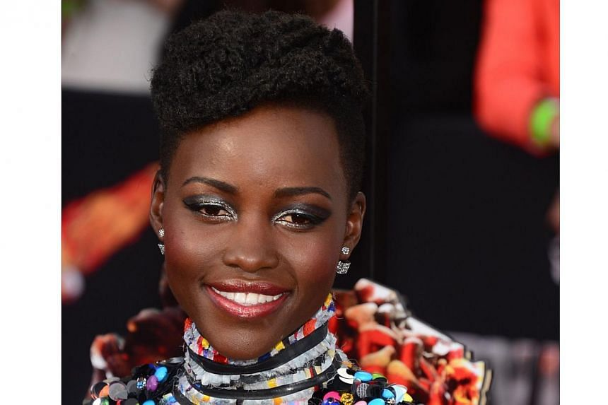 This file picture dated on March 2, 2014 shows actress Lupita Nyong'o celebrating after winning the Best Performance by an Actress in a Supporting Role award for '12 Years a Slave' in the press room during the 86th Academy Awards in Hollywood, Califo