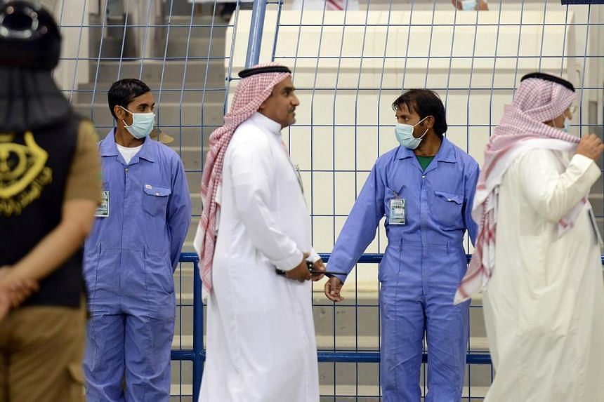 Asian workers wear mouth and nose masks while on duty during a football match at the King Fahad stadium, on April 22, 2014 in Riyadh.King Abdullah was in the Saudi commercial hub of Jeddah on Thursday in a bid to reassure a worried public as th