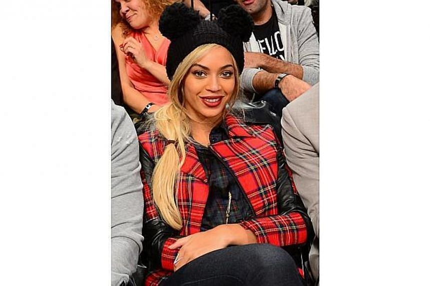 Singer Beyonce watches the NBA game between the Philadelphia 76ers and the Brooklyn Nets at the Barclays Center in New York on Feb 3, 2014. -- FILE PHOTO: AFP