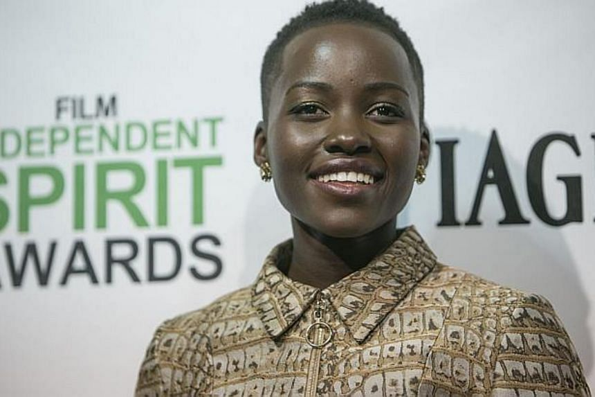 Lupita Nyong'o holds her award for best supporting actress in12 Years a Slave at the 2014 Independent Spirit Awards on on March 1, 2014 in Santa Monica, California. -- FILE PHOTO: AFP