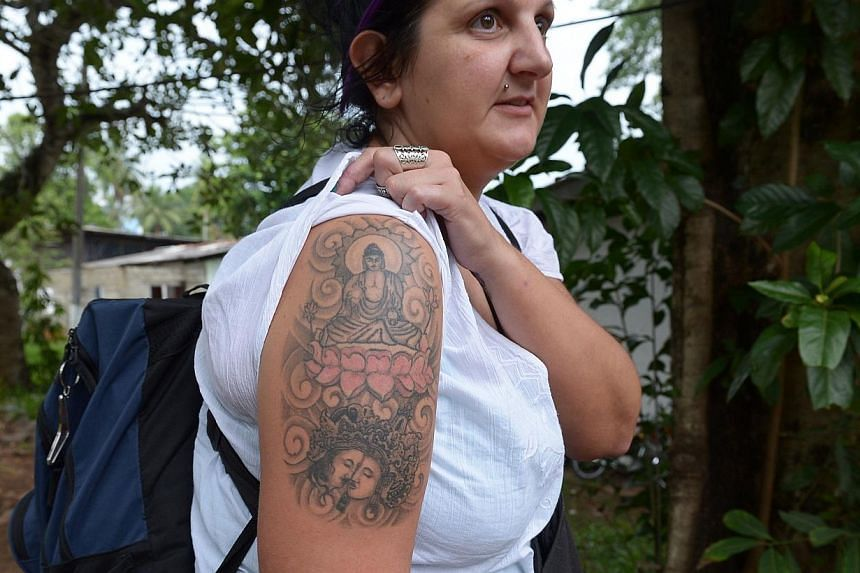 An unidentified British tourist poses for a photograph to display a tattoo of the Buddha on her upper arm, after she was arrested at the country's main international airport and later ordered with deportation for having a tattoo of the Buddha, in Col