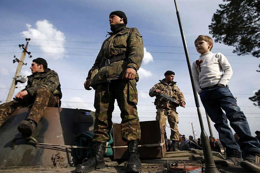 A boy stands with Ukrainian soldiers on a combat vehicle in Kramatorsk, in eastern Ukraine on April 16, 2014.Ukraine's military clashed with pro-Kremlin rebels in two eastern towns overnight, the interior and defence ministries said Thursday. -