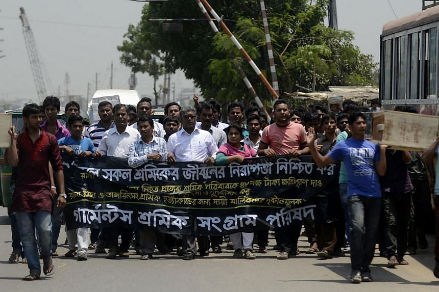 Bangladeshi garment workers and activists carry a mock coffin during a protest in front of the Bangladesh Garment Manufacturers and Exporters Association (BGMEA) office in Dhaka yesterday, April 23, 2014. Today is the first anniversary of the Rana Pl
