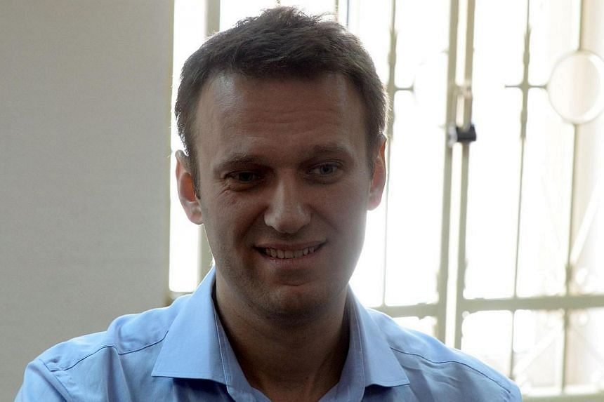 Kremlin critic and opposition leader Alexei Navalny smiles as he stands in a courtroom in Moscow on April 24, 2014.A Russian court on Thursday, April 24, 2014,ruled to extend the house arrest of prominent opposition leader Alexei Navalny