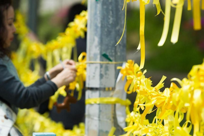 A woman ties yellow ribbons symbolising hope for the safe return of missing passengers on the Sewol ferry onto a main gate of Danwon high school on April 24, 2014. -- PHOTO: AFP