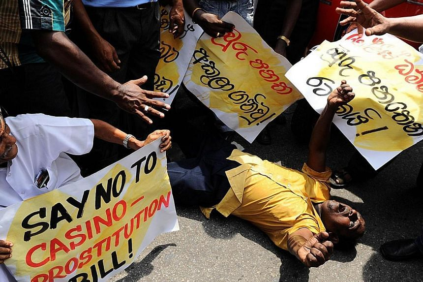 Sri Lanka supporters of the country's main opposition chant slogans and hold banners as they protest outside a casino in Colombo on April 24, 2014.Hundreds of Sri Lankan opposition party members marched in protest in Colombo on Thursday, April