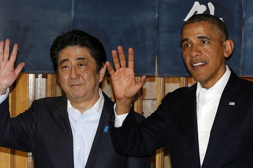 U.S. President Barack Obama (right) waves next to Japan's Prime Minister Shinzo Abe after dinner at Sukiyabashi Jiro restaurant in Tokyo on April 23, 2014. Japanese Prime Minister Shinzo Abe may have hoped to demonstrate his personal ties with Presid