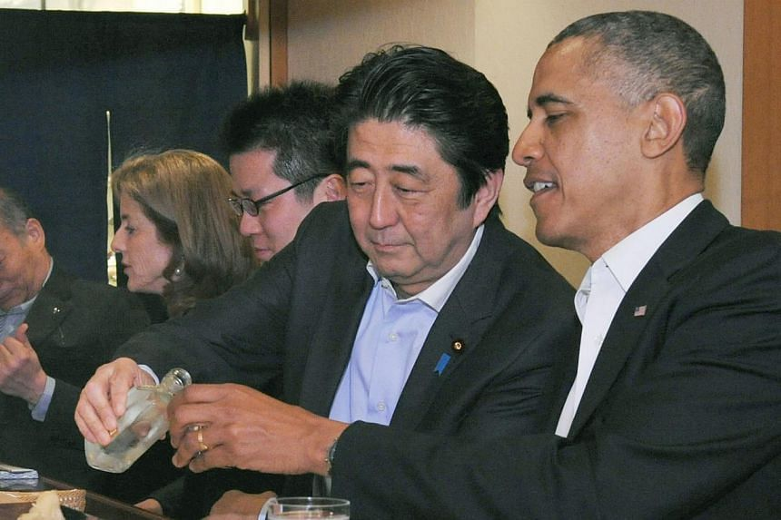 (From right) Mr Obama and Mr Abe sharing a drink at Sukiyabashi Jiro - dubbed the world's best sushi restaurant. -- PHOTO: REUTERS