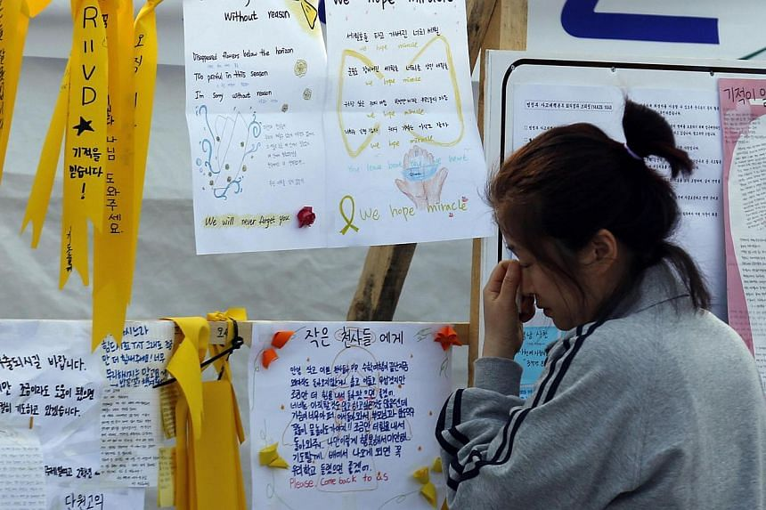 A mother whose teenage child was onboard the capsized Sewol ferry and is missing, cries as she reads messages dedicated to the missing and dead passengers on the ship at a port where many family members wait for news from the search and rescue team i
