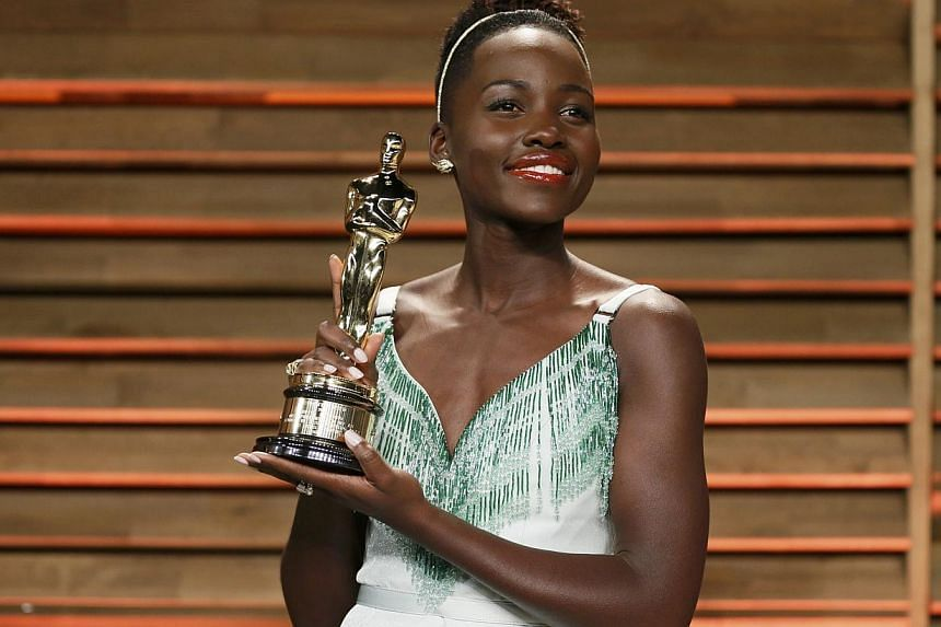 Actress Lupita Nyong'o poses with her best supporting actress award as she arrives at the 2014 Vanity Fair Oscars Party in West Hollywood, California on March 3, 2014. -- FILE PHOTO: REUTERS