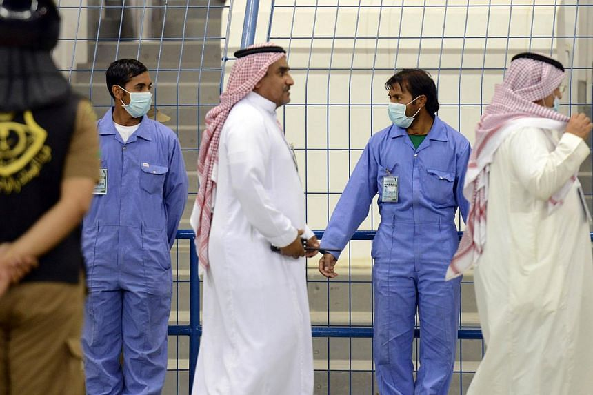 Asian workers wear mouth and nose masks while on duty during a football match at the King Fahad stadium, on April 22, 2014 in Riyadh. -- FILE PHOTO: AFP