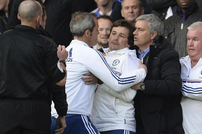 Chelsea's manager Jose Mourinho (2nd right) holds back assistant coach Rui Faria (centre) after he was sent off by referee Mike Dean (left) during their English Premier League soccer match against Sunderland at Stamford Bridge in London on April 19,