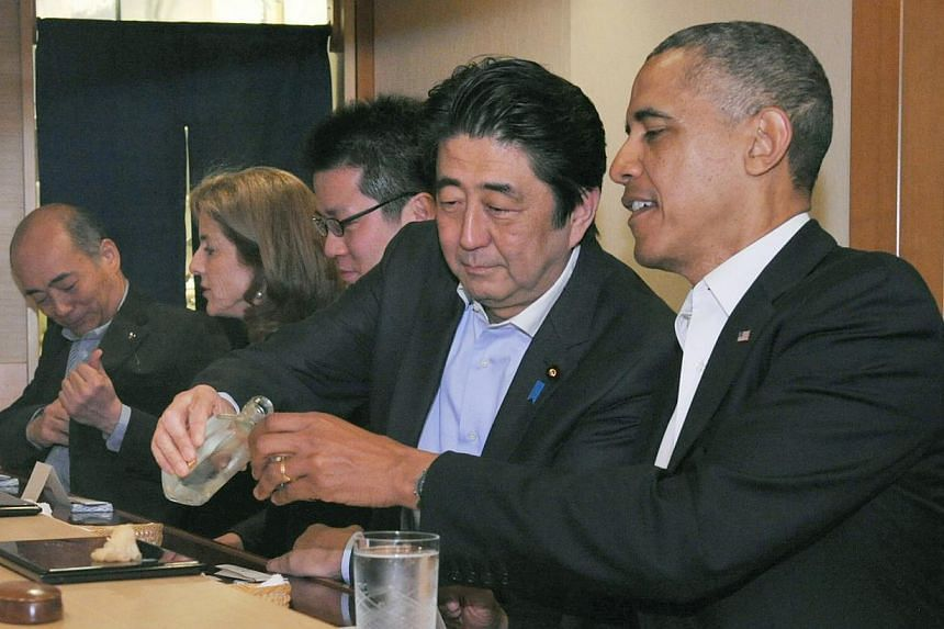 Japanese Prime Minister Shinzo Abe (second from right) pours sake for US President Barack Obama (right) as they have dinner at the Sukiyabashi Jiro sushi restaurant in Tokyo, in this picture on April 23, 2014. -- PHOTO: REUTERS