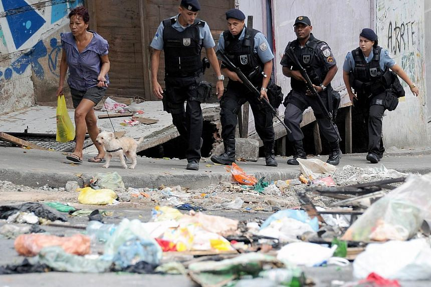 A group of military policemen walking in the streets of the Cantagalo favela, next to Copacabana, where a young dancer was killed last weekend and residents held a protest. -- PHOTO: AFP