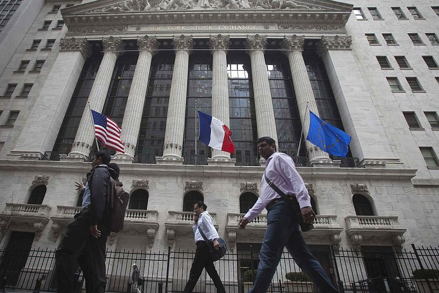 People walk past the New York Stock Exchange as it flies the US, French and Eurozone flags in New York, April 14, 2014.United States stocks dipped on Wednesday to snap a six-session winning streak as gains in Boeing and Gilead were offset by sl