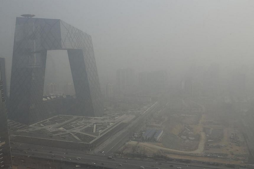The China Central Television (CCTV) building is seen next to a construction site in heavy haze in Beijing's central business district on January 14, 2013. China on Thursday, April 24, 2014, passed amendments to an environmental protection law im