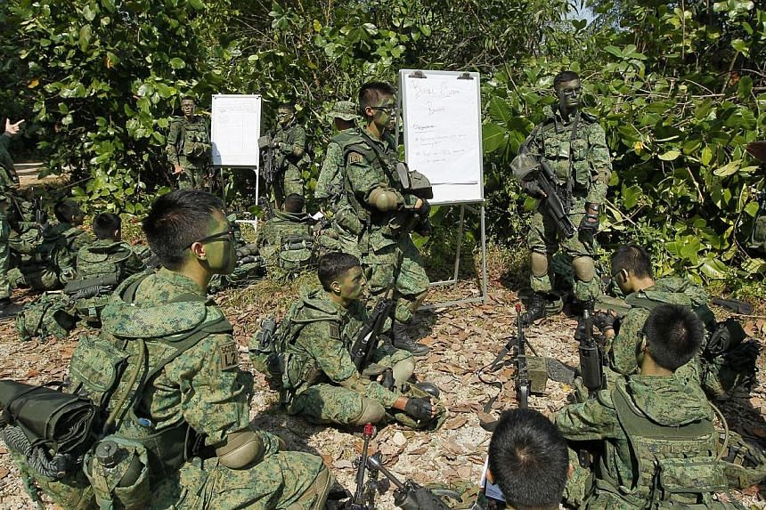 Full-time National Service (NS) specialist cadets from Lima Company, Specialist Cadet School, sharing lessons before a training exercise near Pasir Laba Camp, on July 1, 2013. More support and recognition will be given to operationally ready servicem