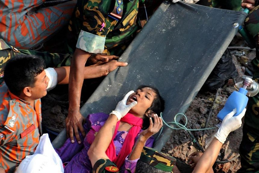 Bangladeshi rescuers retrieve garment worker Reshma Akhter from the rubble of a collapsed building in Savar on the outskirts of Dhaka 17 days after the eight-storey building collapsed, on May 10, 2013. -- FILE PHOTO: AFP