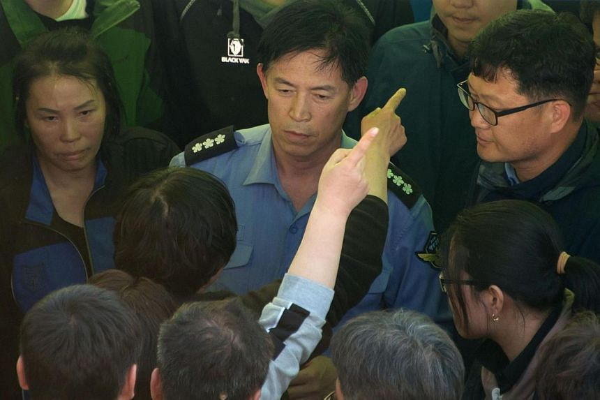 Relatives of victims of the 'Sewol' ferry gesture to vice police chief Choi Sang Han (centre) after they forcibly removed him from an office at Jindo harbour on April 24, 2014. In the hothouse atmosphere of anger and grief triggered by South Korea's