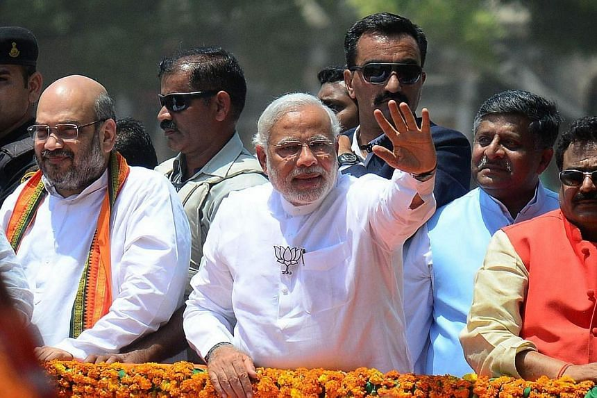 India's main opposition Bharatiya Janata Party (BJP) prime ministerial candidate and Chief Minister of the western Indian state of Gujarat Narendra Modi (centre) waves to supporters as he arrives to file his election nomination papers in Varanasi on