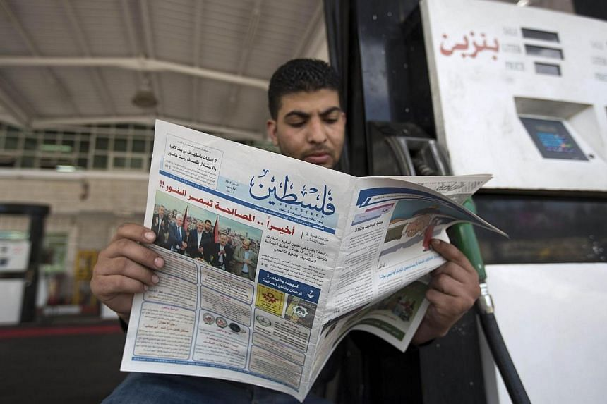 A Palestinian petrol station worker reads a newspaper the day after rival Palestinian leaders from the West Bank and Gaza Strip forged a new reconciliation agreement in Gaza City on April 24, 2014. China's foreign ministry welcomed on Thur