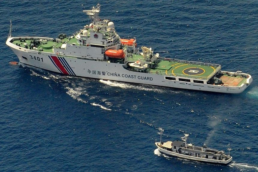 A China Coast Guard ship (top) and a Philippine supply boat engage in a stand off as the Philippine boat attempts to reach the Second Thomas Shoal, a remote South China Sea a reef claimed by both countries on March 29, 2014. -- FILE PHOTO: AFP