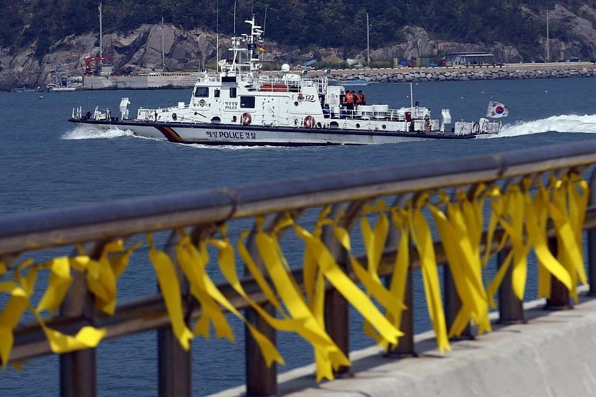 Yellow ribbons dedicated to the missing and dead passengers onboard the capsized Sewol ferry are seen at a port where many family members wait for news from the search and rescue team, as a Coast Guard ship passes behind on its way to the rescue, in