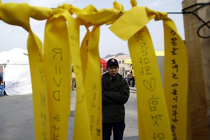 A man looks at yellow ribbons dedicated to the missing and dead passengers onboard the capsized Sewol ferry, at a port where many family members wait for news from the search and rescue team in Jindo on April 24, 2014. --PHOTO: REUTERS