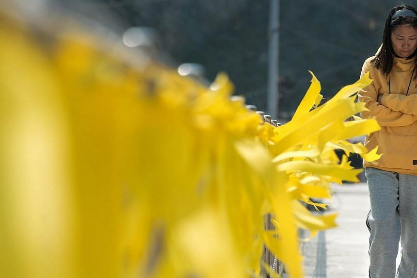 A relative of a missing passenger of the Sewol ferry walks next to yellow ribbons of hope for a safe return of missing passengers, attached on a fence at Jindo harbour on April 24, 2014. -- PHOTO: AFP