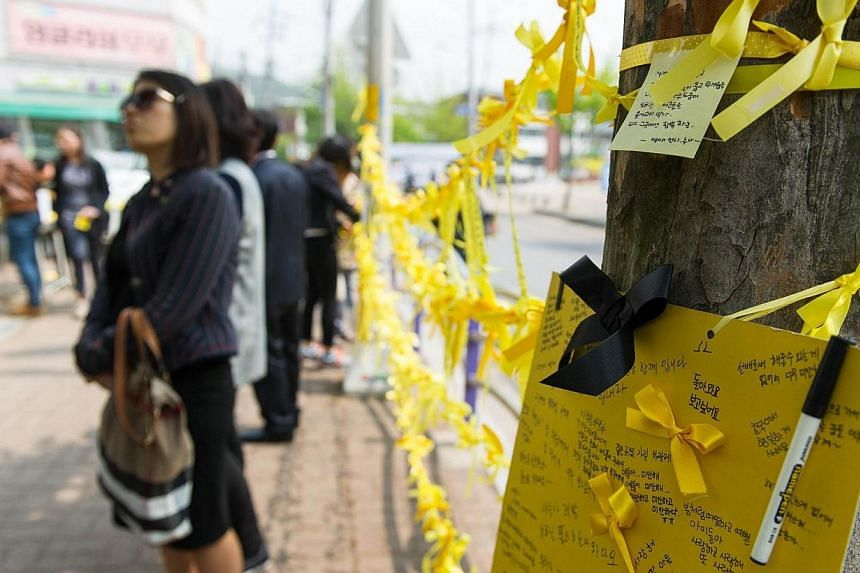Yellow ribbons hang by a road side near Danwon high school where many of the schoolchildren missing from the sunken South Korean ferry Sewol attended in Ansan on April 24, 2014. -- PHOTO: AFP