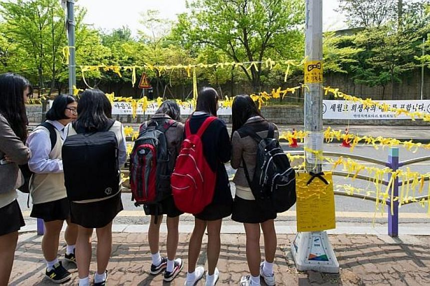 School children hang yellow ribbons by a road side at the main gate of Danwon high school where many of the schoolchildren missing from the sunken South Korean ferry Sewol attended in Ansan on April 24, 2014. -- PHOTO: AFP