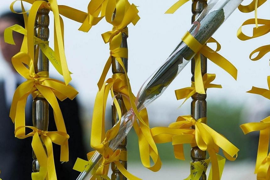 Yellow ribbons symbolising hope for the safe return of missing passengers on the Sewol ferry are displayed on a main gate of Danwon high school on April 24, 2014. -- PHOTO: AFP
