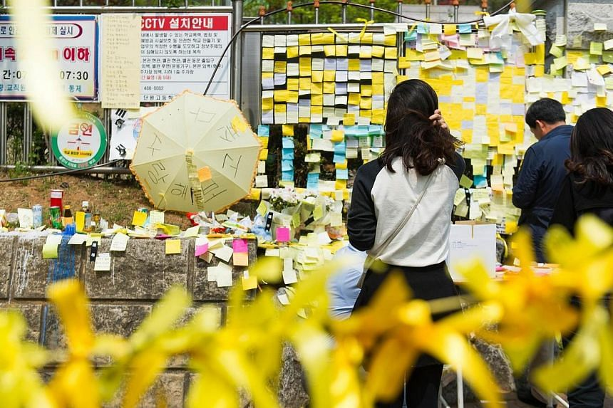 Pedestrians pray in front of a makeshift memorial at the main gate of Danwon high school in Ansan on April 24, 2014 where many of the schoolchildren missing from the sunken South Korean ferry Sewol attended. -- PHOTO: AFP