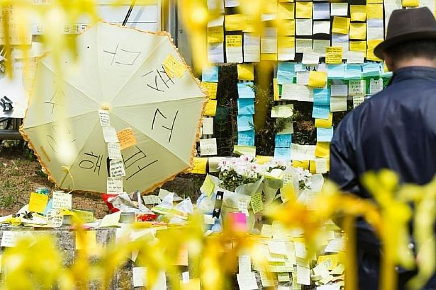 A man prays in front of a makeshift memorial at the main gate of Danwon high school in Ansan on April 24, 2014 where many of the schoolchildren missing from the sunken South Korean ferry Sewol attended. -- PHOTO: AFP