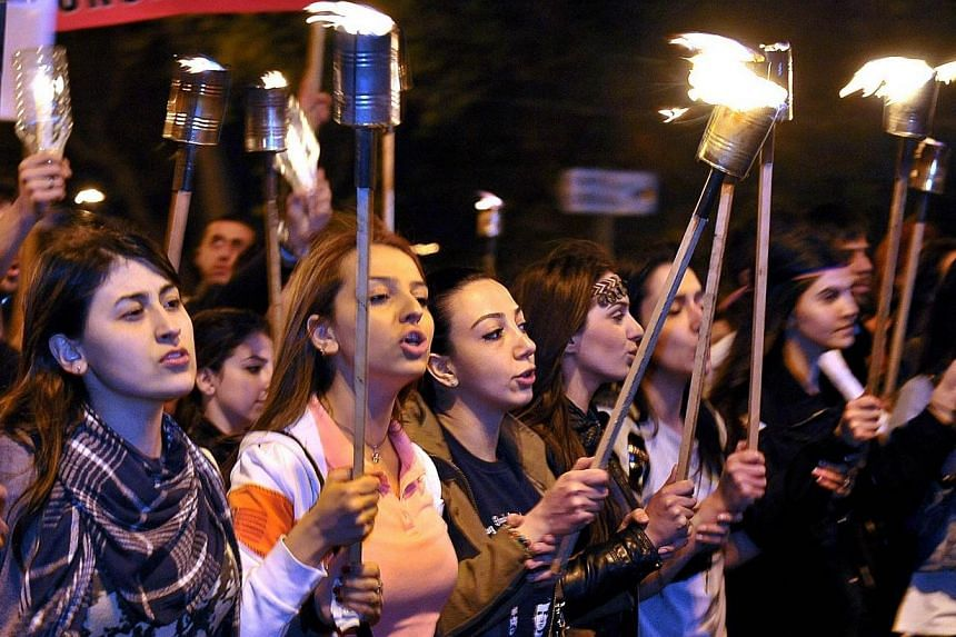"""Armenian women carry torches to commemorate the 99th anniversary of the Ottoman Turkish massacre of Armenians, in Yerevan on April 23, 2014.Armenian President Serzh Sarkisian on Thursday, April 24, 2014, accused Turkey of an """"utter denial"""" in f"""