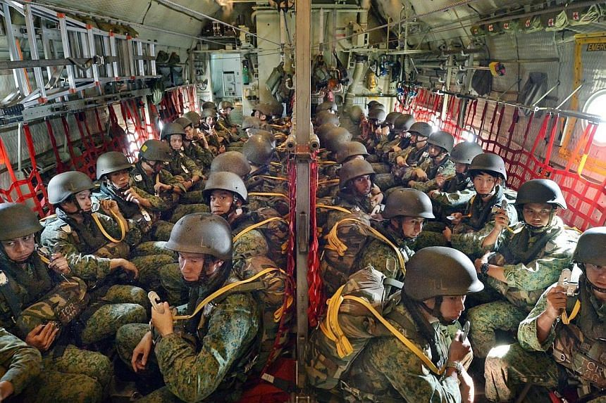 Packed into the cavernous belly of the C-130 Hercules transport aircraft, paratroopers clutch their static lines as they wait for the aircraft to reach jump altitude. -- ST PHOTO: ALPHONSUS CHERN