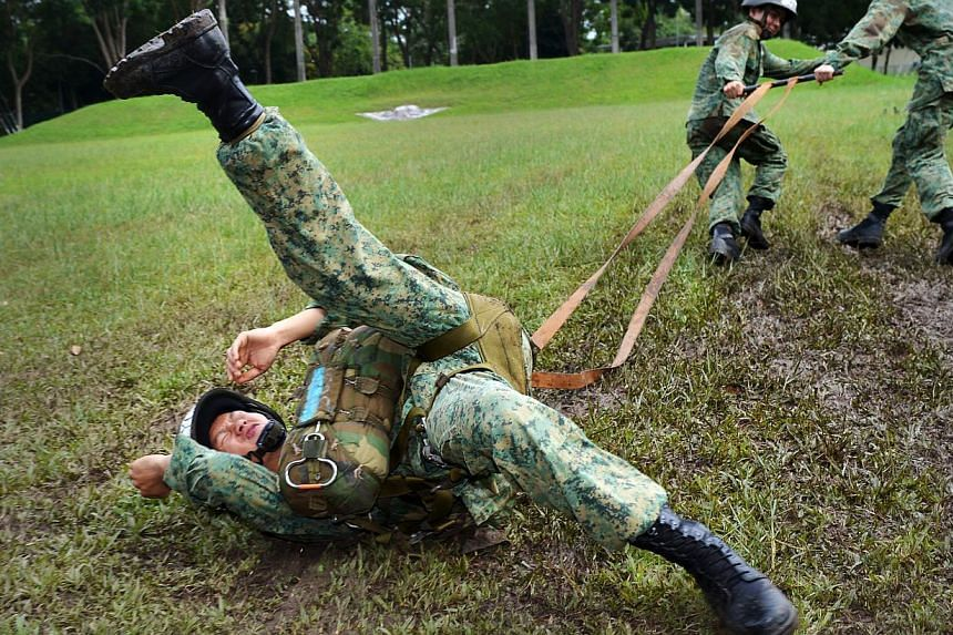 Trainee J. Y. Chen is hauled through a muddy field by eager coursemates simulating what happens when a gust of wind catches his open parachute on landing. Chen must quickly release his harness buckles, collapsing his canopy to stop it dragging him ac