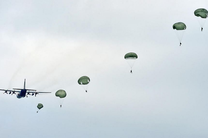 """A string of parachutes bloom behind the old but reliable C-130 Hercules transport which carries 56 paratroopers and is the SAF's mainstay for dropping soldiers into combat. Introduced by the United States Air Force in the late 1950s, the """"Charlie"""" ha"""