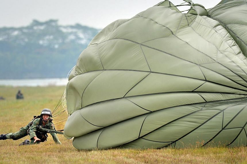 Corporal Joel Tang scrambles to deflate his parachute canopy before it catches air and drags him across the field. -- ST PHOTO: ALPHONSUS CHERN