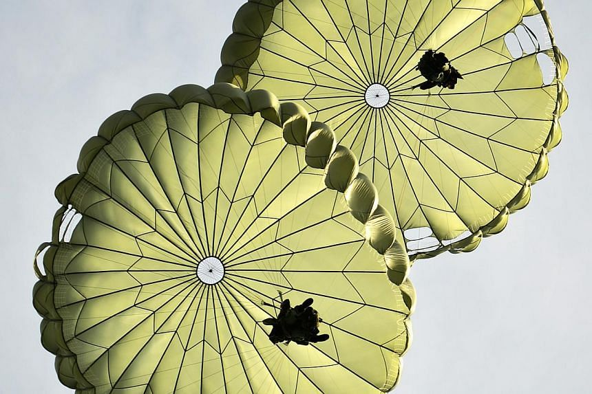 Looking like a pair of water lily pads, two parachutists drift over the drop zone after jumping out of a Chinook helicopter. -- ST PHOTO: ALPHONSUS CHERN
