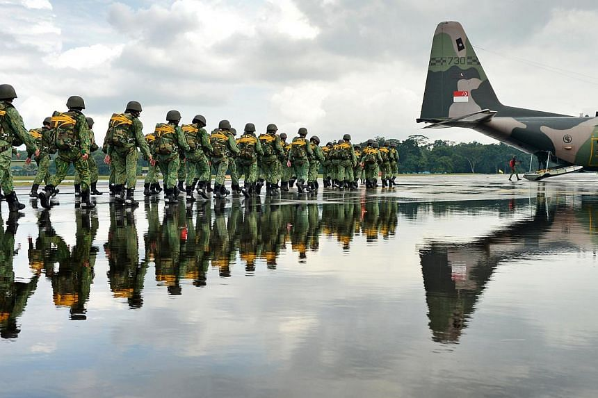 Led by a jumpmaster, parachutists march to a C-130 Hercules transport plane at the Paya Lebar Air Base for their first jump of the day. -- ST PHOTO: ALPHONSUS CHERN