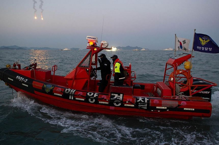 Coastguards ride a boat during recovery operations at the site of the Sewol ferry, off the coast of the South Korean island of Jindo on April 24, 2014. Dive teams raced on Friday to pull more than 100 bodies from a sunken South Korean ferry as storm