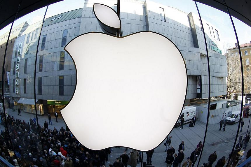 People wait on a street in front of an Apple store as they await sales of the new iPad in the Apple store in Munich in this file photo taken March 16, 2012.Four major tech companies including Apple and Google have agreed to settle a large antit