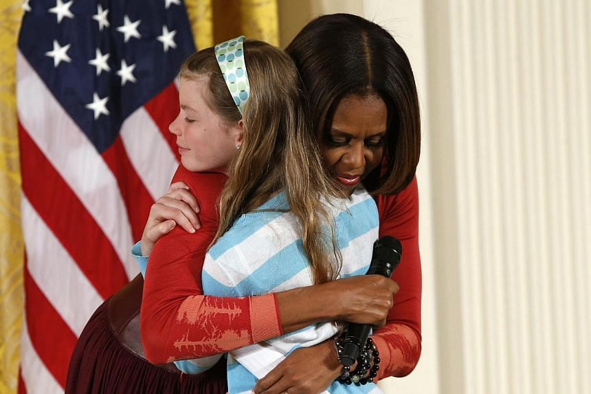 First Lady Michelle Obama hugs Charlotte Bell, 10, who gave the first lady her father's resume and said he had been out of work for three years, as Michelle Obama was speaking with children of Executive Office employees at the White House's annual Ta